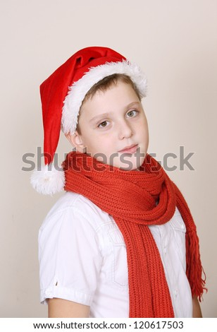 A cute boy in a red christmas hat and scarf - stock photo