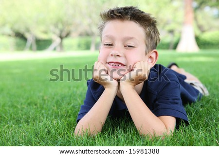 A cute boy relaxing on the grass in the park - stock photo