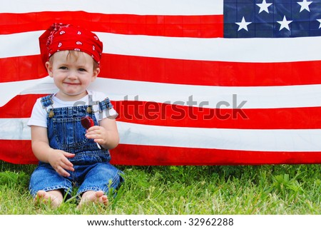 A cute boy sitting in front of an american flag - stock photo