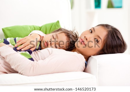 A cute boy sleeping tight in his mother's arms. - stock photo