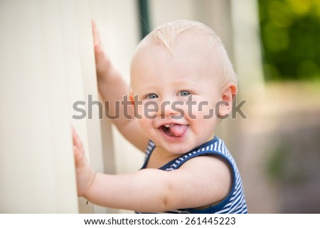 A cute cheeky baby boy sticks his tongue out - stock photo
