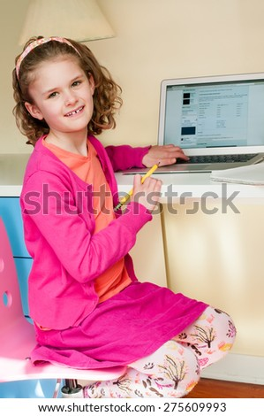 A cute elementary aged little girl sits at a desk while researching information on a laptop.  She holds a pencil and a notebook is open on the desk.  She is wearing a bright pink and orange outfit. - stock photo