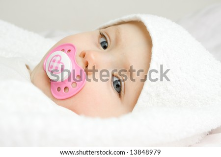 A cute face of a baby covered with soft, white towel. - stock photo