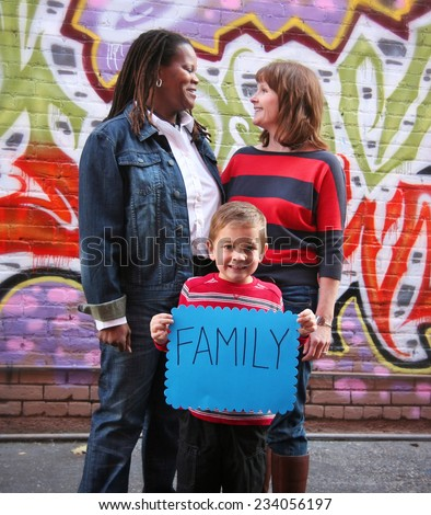 a cute family holding a sign that read family  - stock photo