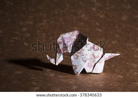 A cute floral origami elephant isolated on craft paper background. - stock photo
