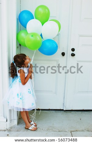 A cute girl holding a bunch of balloons - stock photo