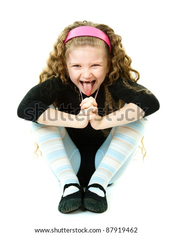 A cute girl sitting and showing her tongue isolated in a white background - stock photo