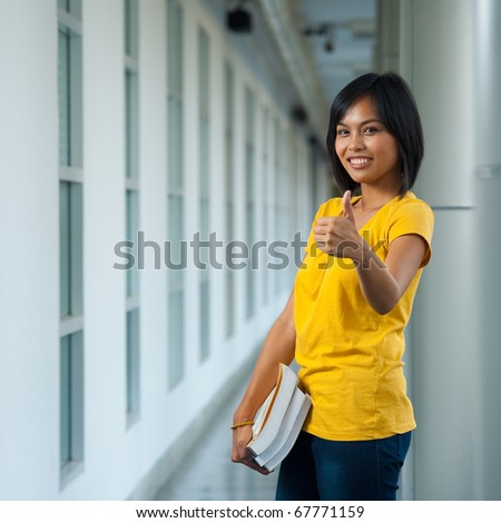 A cute happy college student holding books smiles while giving a thumbs up on a modern university campus.  20s female Asian Thai model of Chinese descent. - stock photo