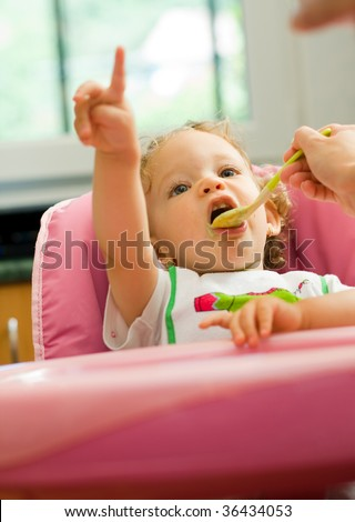 A cute little baby fed by her mother, eating spinach, pointing upward at somthing. - stock photo