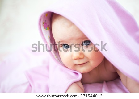 A cute little baby girl is staring up and is hiding under a pink sheet blanket. - stock photo