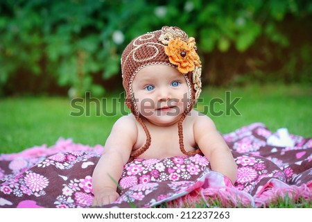 A cute little baby is looking into the camera and is wearing a brown hat. The baby could be a boy or girl and has blue eyes. use it for a parenting or love concept.  - stock photo