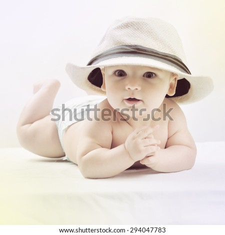 A cute little baby is looking into the camera and is wearing a white hat. The beautiful baby could be a boy or girl - stock photo