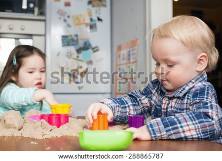 A cute little blond boy and a little girl play with kinetic sand at home - stock photo