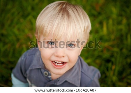 A cute little blonde 1 year old boy outdoors looking up at the camera with a big smile. - stock photo