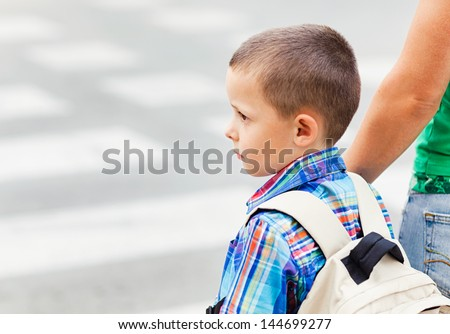 A cute little boy and his mother waiting to cross the street on their way to school. - stock photo