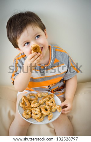 A cute little boy eating a fresh baked cookie - stock photo