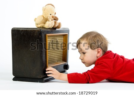 A cute little boy playing with a vintage radio. - stock photo