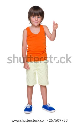 A cute little boy shows his thumb up on the white background - stock photo