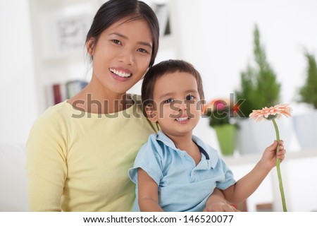 A cute little boy sitting on his mother's lap and holding a beautiful flower for her. - stock photo