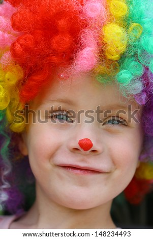 A cute little child dressed up in a clown costume and smiling - stock photo