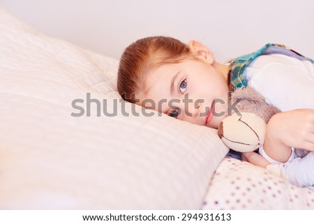 A cute little girl lying on her bed with her teddy - stock photo
