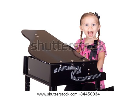 A cute little girl plays with her piano. - stock photo