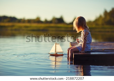 A cute little girl sitting on the pontoon bridge on the river with a toy ship in hands in a warm sunny summer day. - stock photo