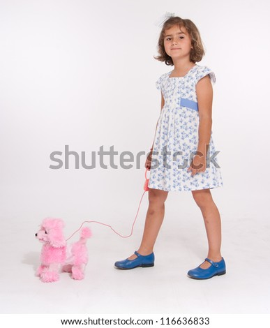 A cute little girl walking her toy dog - stock photo