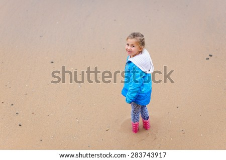 A cute little girl wearing warm clothes- a jacket and gumboots standing in the sand at the beach and looking up with a sandy beach at the background. - stock photo