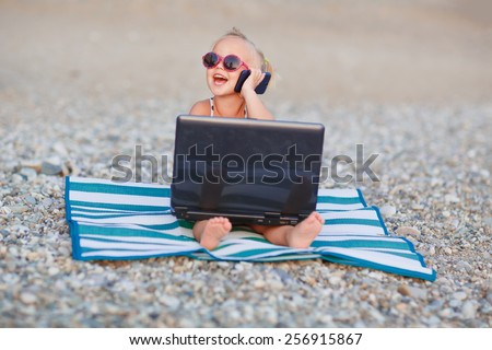 A cute little happy girl in pink sunglasses sitting on the striped blue and white mat with a laptop on the beach on a warm summer day. Holiday on a seashore concept. Funny kids. Sea. Ocean. - stock photo
