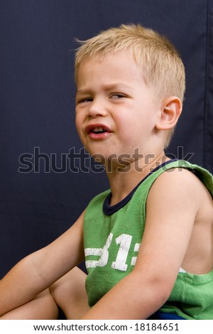 A cute little 3 year old boy with a sad or angry face. - stock photo