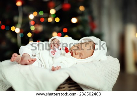 A cute newborn baby in white clothes sleeping in a basket on the floor against a twinkling Christmas Tree with decoration. New Year's Eve. - stock photo