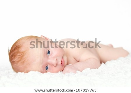 A cute newborn / 4 weeks old baby on a white carpet. - stock photo