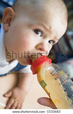A cute one year old baby is drinking from the nursing bottle while he is looking at her mother. The entire shot is soft, the DOF is very shallow, only the closest eye and the teat are sharp. - stock photo