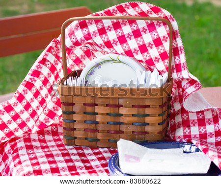 A cute picnic utensil basket and tablecloth on a breezy day - stock photo