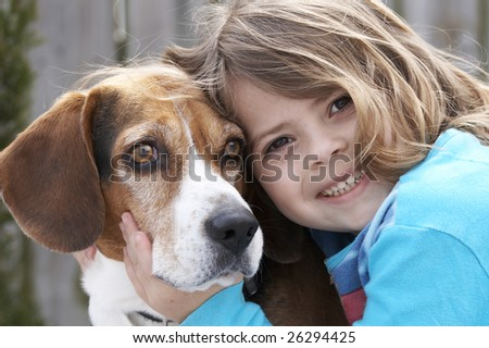 a cute picture of a young beagle and a little girl - stock photo