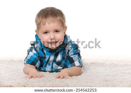 A cute preschool boy is lying on the white carpet - stock photo