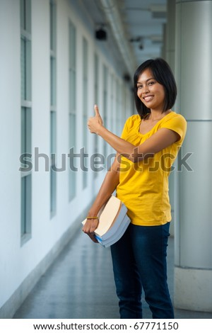 A cute smiling college student gives the thumbs up in a beautifully repetitive hallway on a modern university campus.  20s female Asian Thai model of Chinese descent. - stock photo