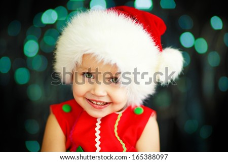 A cute smiling 2-years old girl in a Santa hat and red dress against Christmas glitter close-up - stock photo