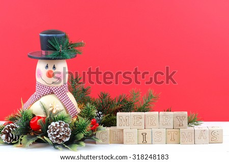 A cute snowman decoration with lamp inside is surrounded by holly, pine, pine cones and Christmas decorations. Bright red background. Merry Christmas message in letter blocks with copyspace above - stock photo