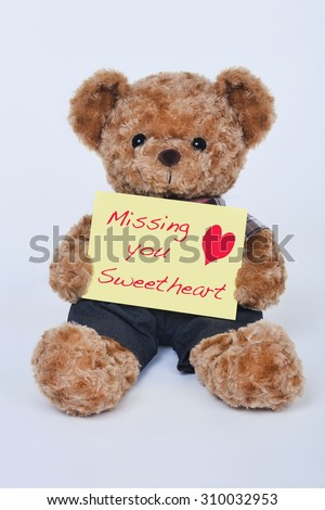 A cute teddy bear holding a yellow sign that says Missing my sweetheart isolated on a white background - stock photo