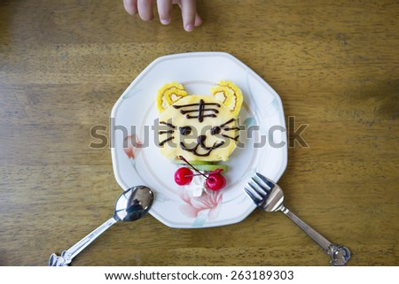 A cute tiger decorated cake with a kid's hand background. - stock photo