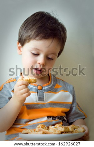A cute two years old boy with plate of fresh baked cookies - stock photo