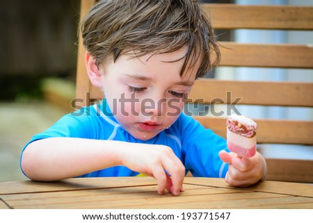A cute 3 year old boy with a lolly on a hot summers day - stock photo