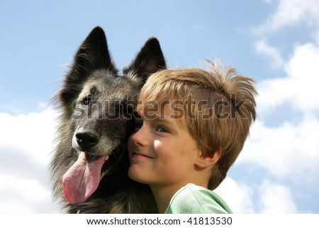 a cute 7-years old boy with his dog, a Belgian shepherd, photographed in the summer sun with blue sky and clouds in the background - stock photo