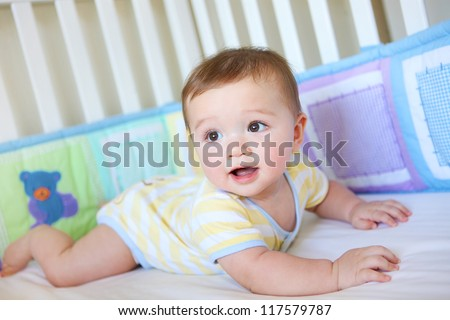 A cute young baby boy in a crib smiling - stock photo