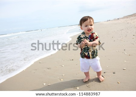 A cute young baby boy playing in the sand at the beach - stock photo