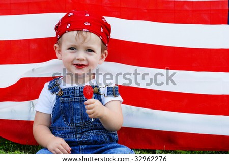 A cute young boy eating a sucker in front of an american flag - stock photo