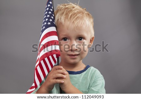 A cute young boy holds an American flag next to his head. - stock photo