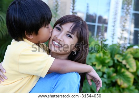 A cute young boy kissing his mother outside home - stock photo